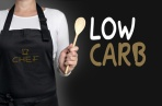 low carb cook holding wooden spoon background concept.