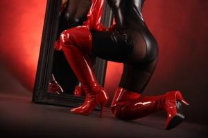 Frau in roten Stiefeln kniet vor Spiegel