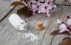 Globuli mit Blüten auf rustikalem Tisch