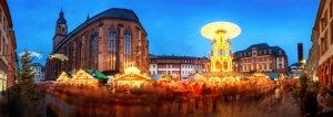 Christmas market in Heidelberg, Germany, a panorama shot at dusk showing illuminated kiosks, historic architecture and blurred people
